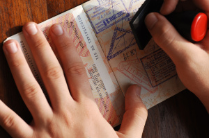a person stamping an open passport, immigration