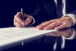 man signing a legal document