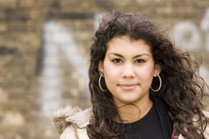 Dark haired girl with hoop earrings, outside, looking at the camera.