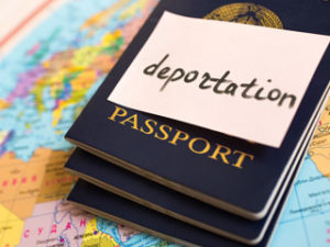 Deportation on a post it placed on a passport on top of a map.